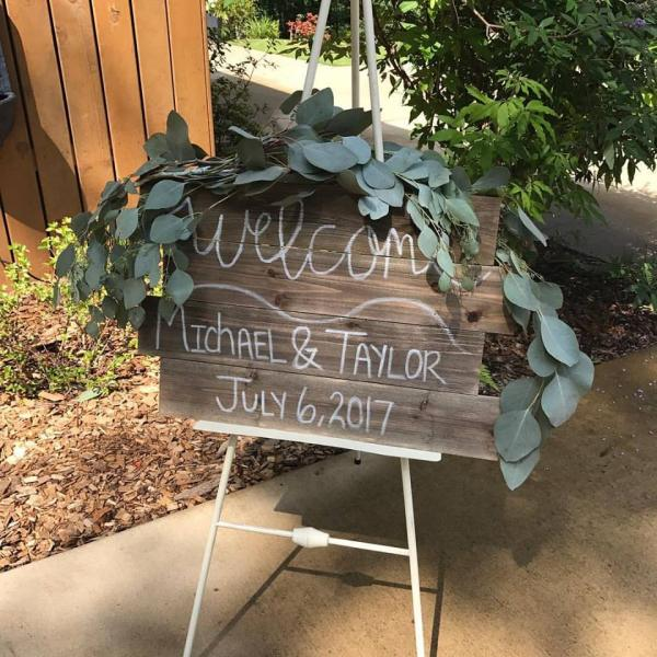 [Image: Wedding signs to show us the way, welcome us in or inspire us with a loving quote is often accented with greenery to soften the edges and add texture. ]