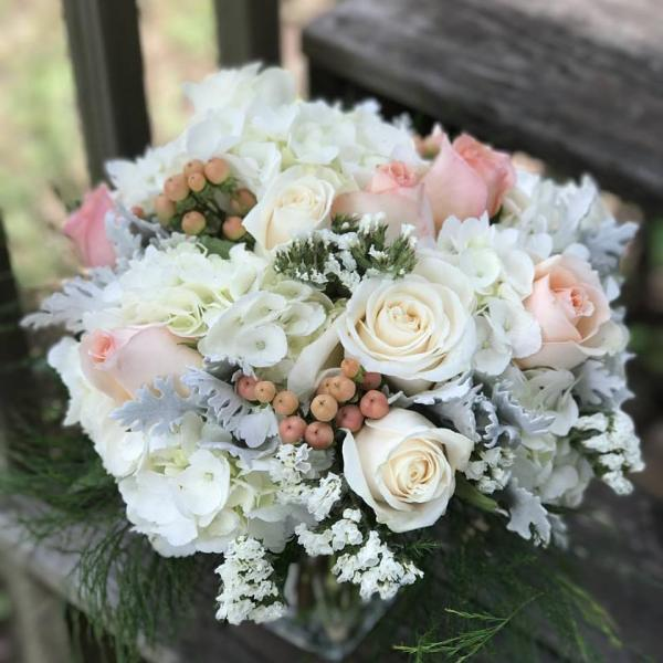 Peach roses nestled in shades of white and grey.]