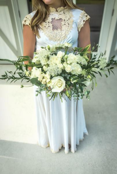 Lush greenery and a mixture of white flowers create a perfect bridal boquet.