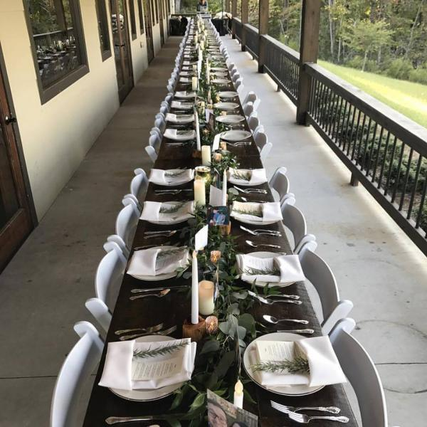 [Image: We shall all dine together at this 70 foot table accented with garlands of greenery and candles.  Venue: Blue Mountain Winery in Dahlonega]